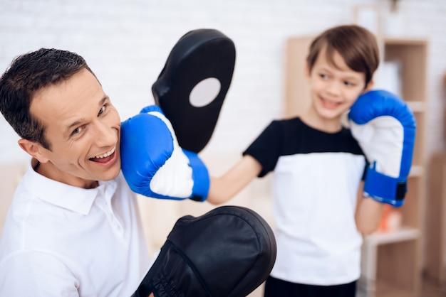 小さな男の子はボクシンググローブでパパを倒します。