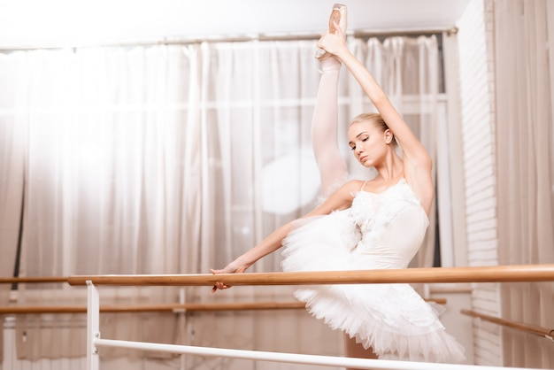 Девушка-балерина стоит в студии и тренируется.