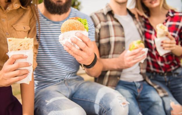Люди сидят в парке и едят фаст-фуд.