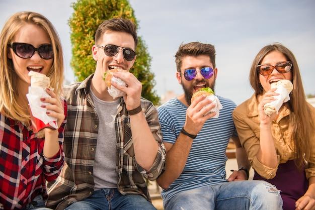 人々は公園に座って食べ物を食べています。