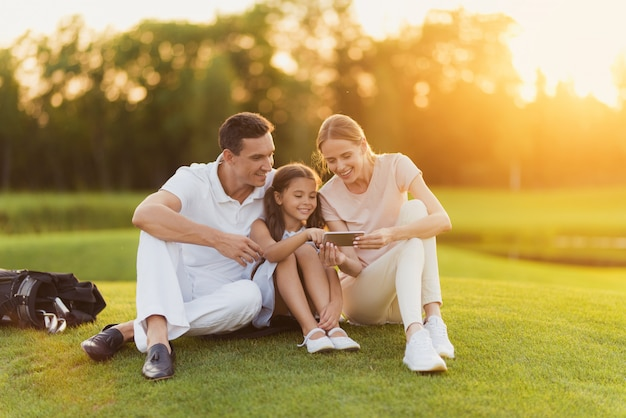 家族はゴルフの写真を見た後休んでいます。