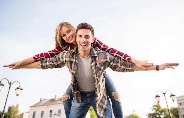 若い女の子は男の肩に座って飛ぶ。