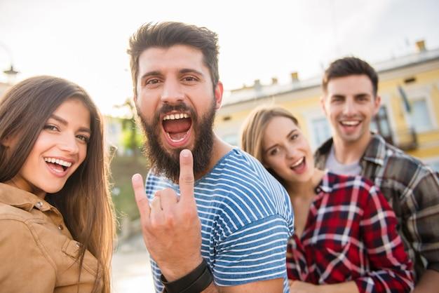 ひげを持つ若い男が親指を現しています。