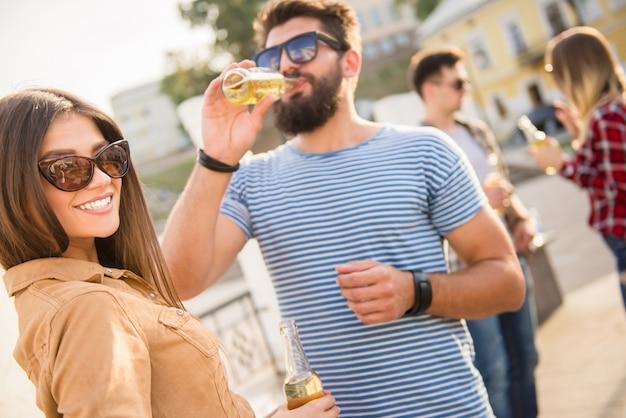 Мужчина общается с девушкой на улице и пьет.