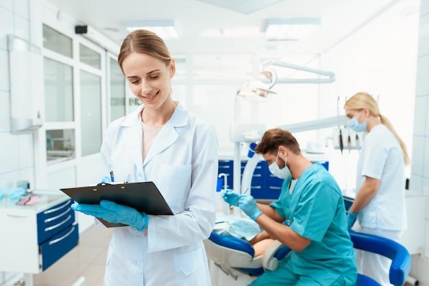 看護師が歯科医を背景にポーズ