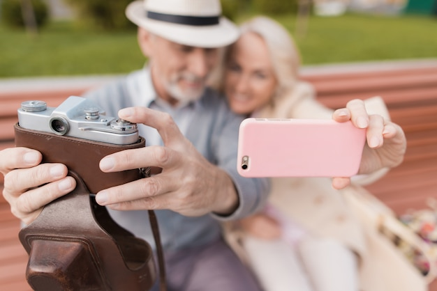 引退した人々のカップルがモールのベンチに座っています。
