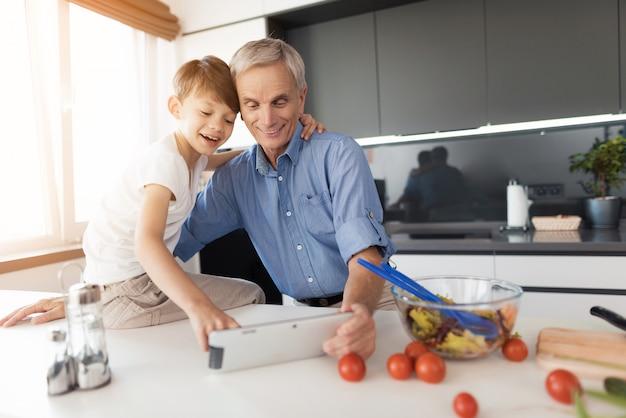 老人と男の子が台所に座っています。