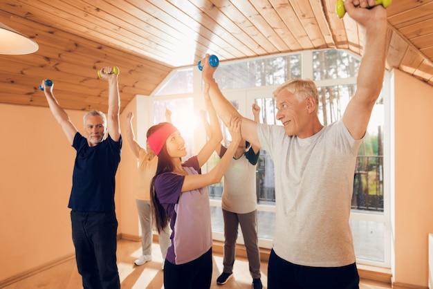 Молодой инструктор с пожилыми людьми занимается с ними
