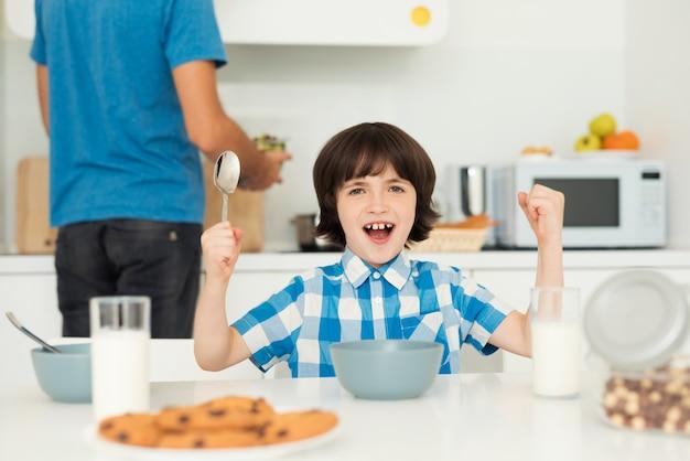父と息子は、明るいキッチンで朝食をとります。