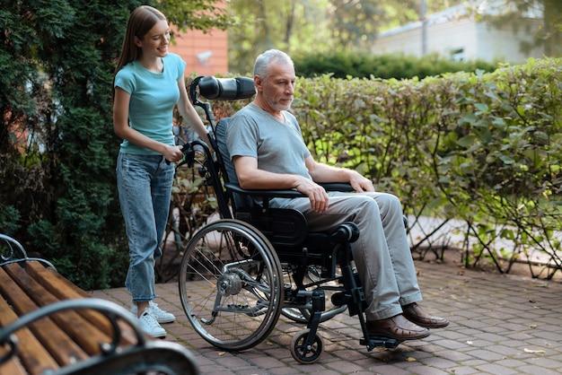 老人は車椅子に座っています。