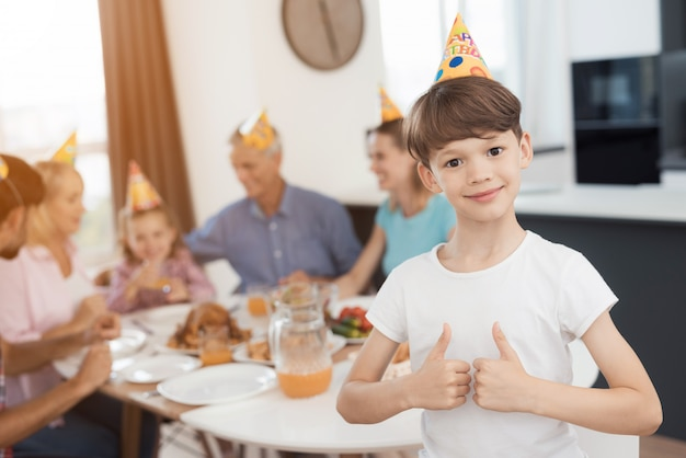 親指を立てる少年はお祝いテーブルの背景にポーズをとって