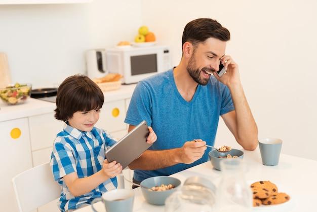 人々は男の子のお母さんとタブレットで通信します