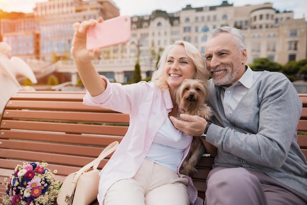 Пожилая пара гуляет на площади со своей маленькой собачкой