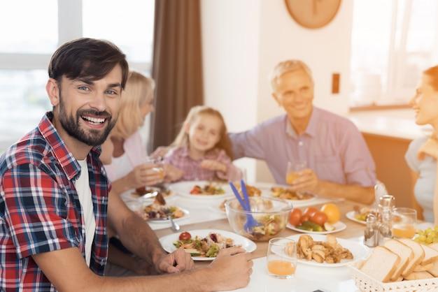 一人の男が彼の家族を背景にポーズ