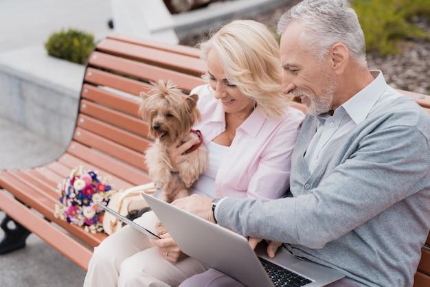 Пожилая пара отдыхает, сидя на скамейке на площади