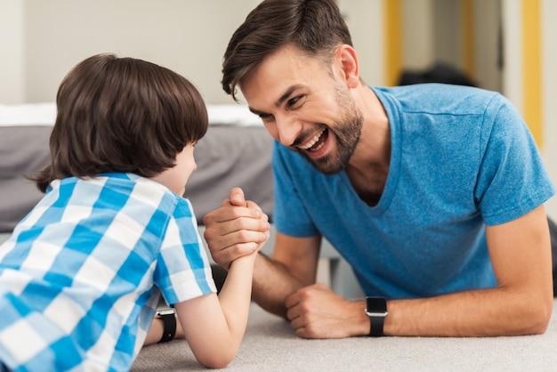 Отец и сын соревнуются в армрестлинге, лежа на полу