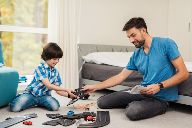 Отец и сын соревнуются в гонках на детских машинах