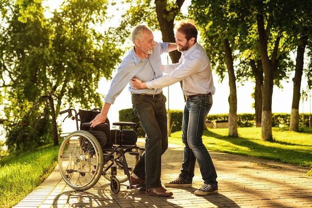 息子は祖父が松葉杖で微笑む男の上に立つのを手伝う