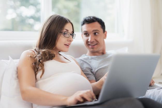 妊娠中の女性と男性がベッドに横になっています