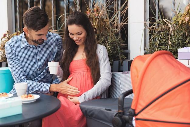 男性と妊娠中の女性はカフェのテーブルに座っています。