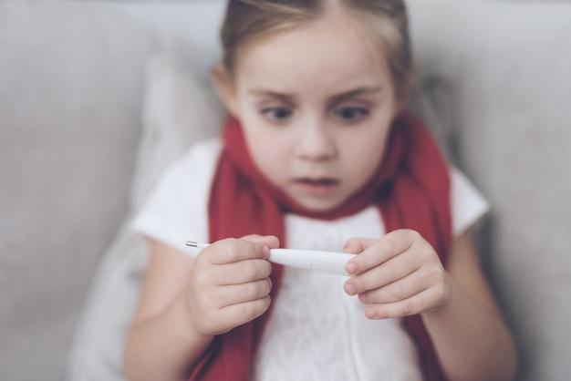 女の子は温度計を見て、それは高温を持っています