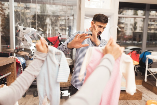 男性と妊娠中の女性は店でベビー用品を選ぶ