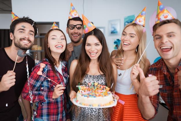 誕生日の女の子はろうそくでケーキを持っています。