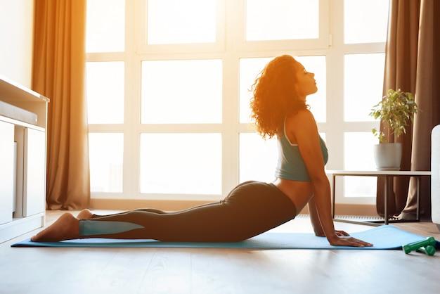 Афро американская девушка делает упражнения йоги на ковер