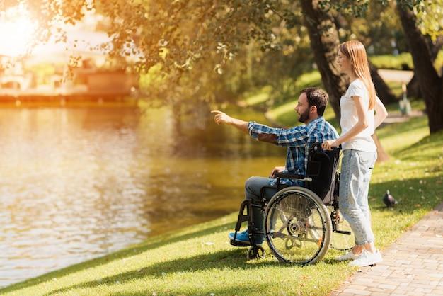 女性が車椅子の男性と公園を散歩しています。