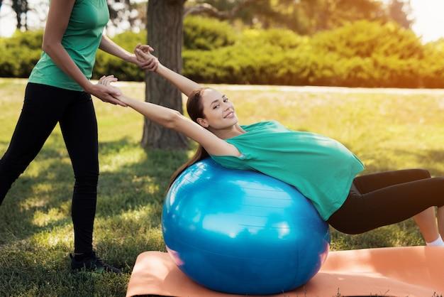 Женщина делает упражнения на синем шаре для йоги