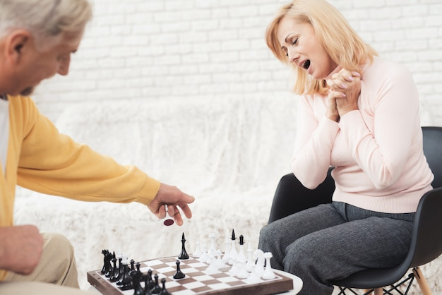 老人のカップルが自宅でチェスをする