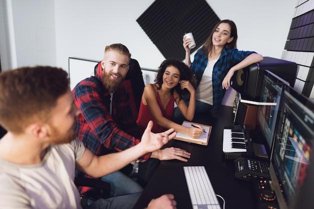 Два певца и звукорежиссера в студии звукозаписи