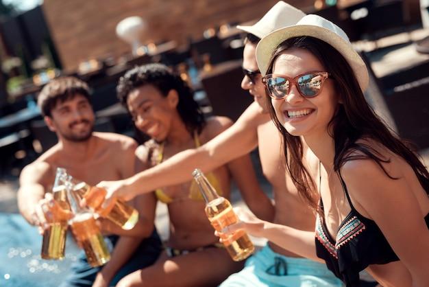 プールサイドでアルコール飲料を持つ友人