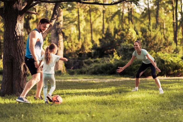 公園で幸せな家族がサッカーをしています。