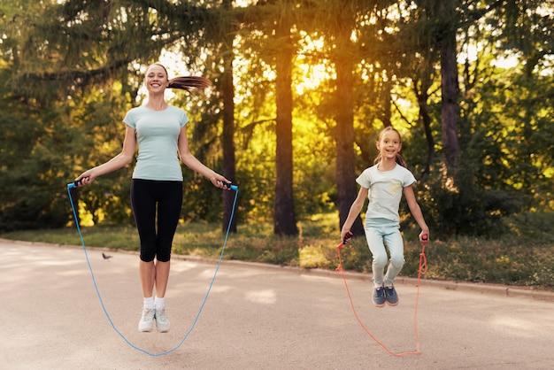 Девочка и ее мать прыгают через скакалку на дорожке в парке