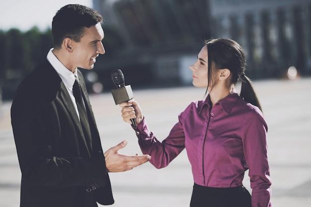 ビジネスの男性が女性にインタビューを与える