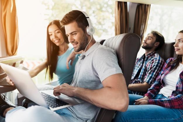 男はバスの中でラップトップに取り組んでいます