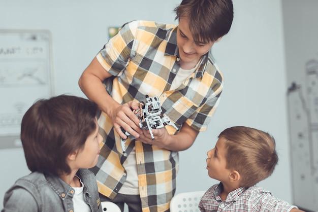 若い男は二人の少年に灰色のロボットを連れてきた