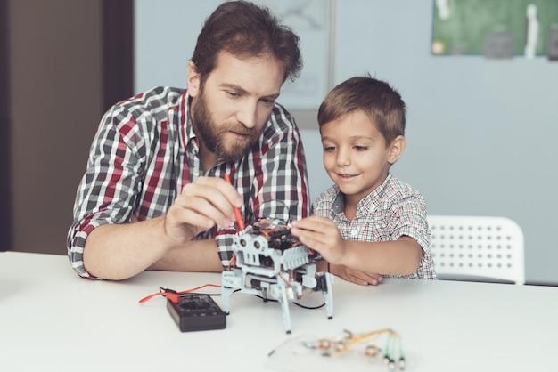 Мужчина и маленький мальчик измеряют производительность робота