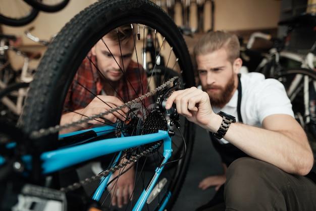 若い男が彼の自転車を修理するためにワークショップにやって来た