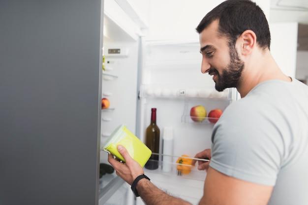 スポーティな男は台所に立ち、新鮮な野菜を取ります