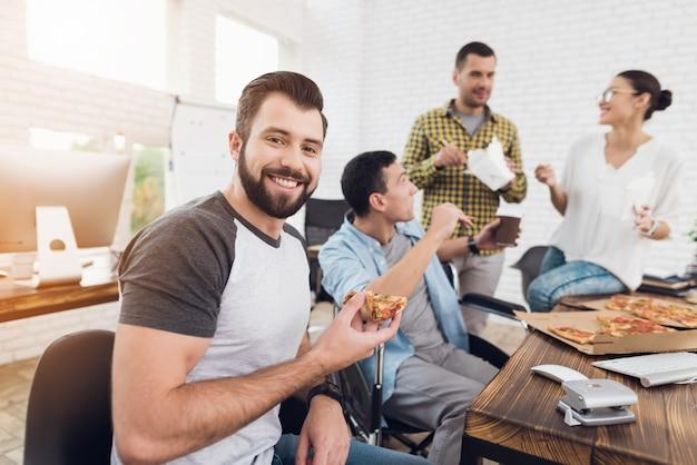 笑顔のひげを生やした男はオフィスでピザを食べています。