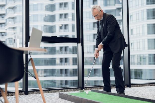 男は窓の背景に立っているし、ゴルフクラブを保持しています