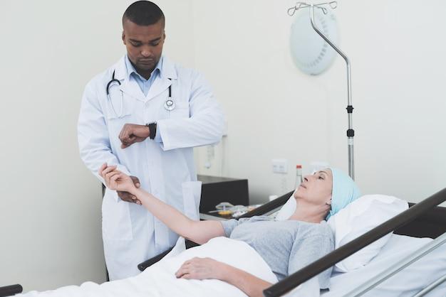 医者は女性の脈拍を測定しています