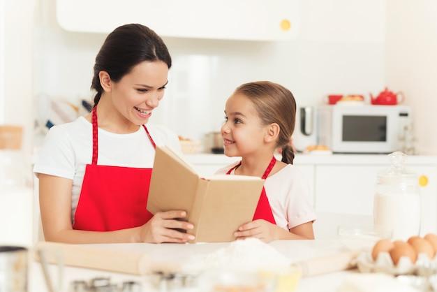 ママと娘は料理本のレシピを見ています。