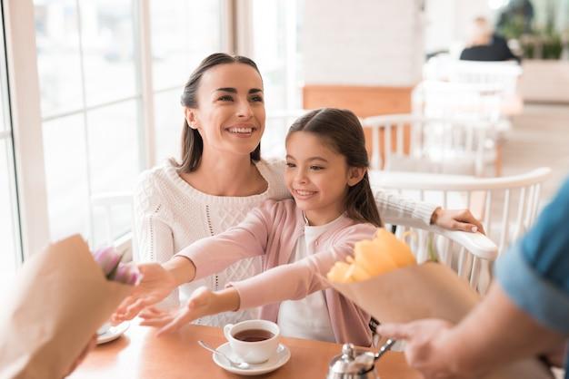 幸せな興奮している女の子のお母さんと娘と花。