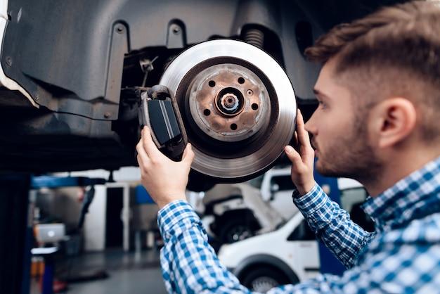 若いメカニックはガレージで自動車用ハブを修復します。