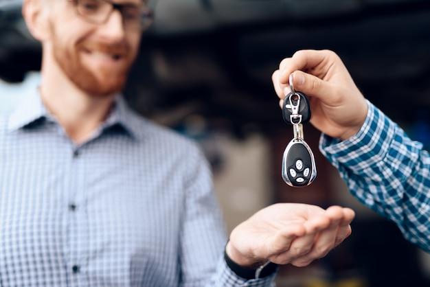 Механик дает ключи владельцу автомобиля в гараже.