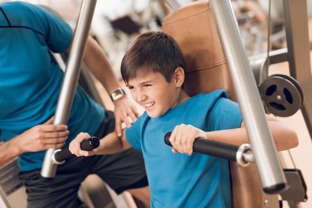Сын делает грудь упражнения в тренажерном зале.
