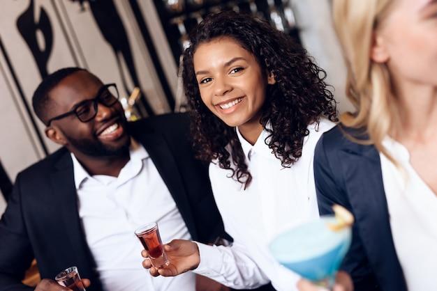 Четверо парней и девушек пьют коктейли в баре.